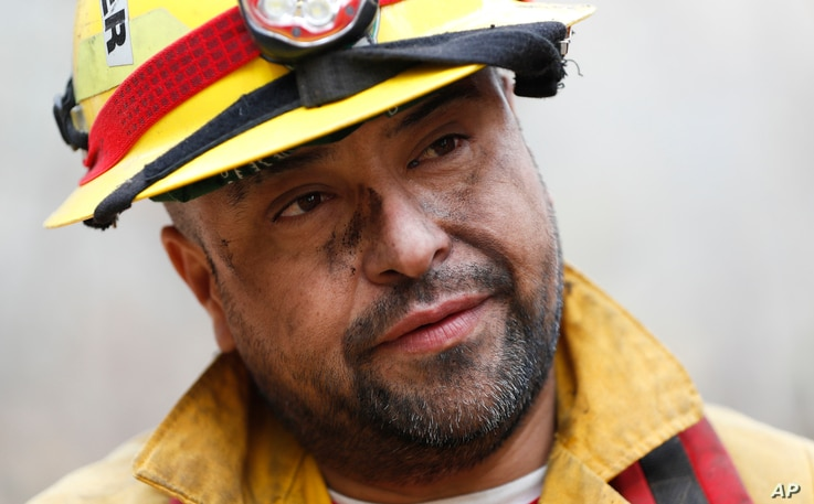 Firefighter Mark Tabaez speaks with a reporter after battling a wildfire in Clayton, Georgia, Tuesday, November 15, 2016.