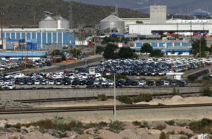 FILE - Cars sit at the General Motors plant in Ramos Arizpe, Mexico, Nov. 21, 2013. General Motors employs cheaper labor in Mexico, paying workers an average of about $10 an hour, compared to the $33 average autoworkers make in the U.S.