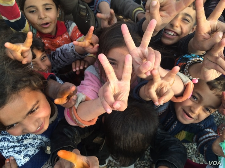 Children all over the region re-captured by the Iraqi Army flash victory signs, saying they have been freed of Islamic State militants.  Khazir Camp, Kurdish Iraq on Dec. 1, 2016. (H.Murdock/VOA)