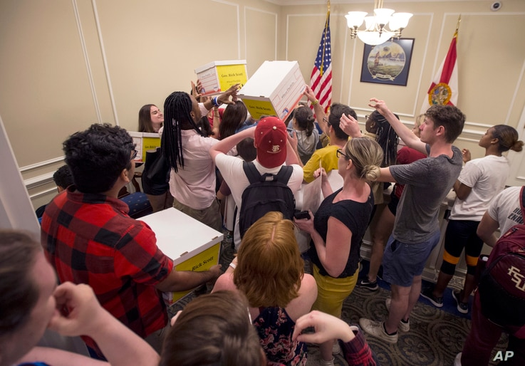University students pass around boxes of petitions for Florida Governor Rick Scott in the governor's office inside the Florida Capitol in Tallahassee, Feb 21, 2018. A week after a shooter killed more than a dozen people in a Florida high school, thou...