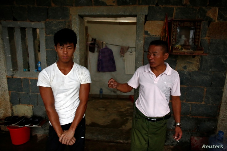 FILE - Shi Shenwei, left, listens to his uncle and foreman Shi Lijia in an old farm house that serves as a dormitory for workers on a nearby construction site in Fujian Province, China, September 28, 2016.