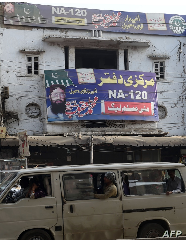 Pakistani commuters drive past an abandoned office of the Milli Muslim League (MML) that was launched in August 2017 by Hafiz Saeed's Jamaat-ud-Dawa (JuD) — the charity wing of militant group Lashkar-e-Tayyiba (LeT) — in Lahore, April 3, 2018.