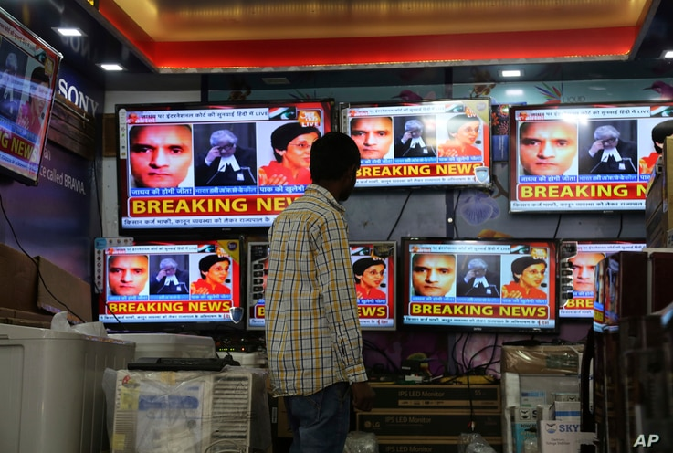 FILE - An Indian boy watches as television channels show news about International Court of Justice hearing the case of Indian naval officer Kulbhushan Jadhav at a shop in Jammu, India, May 15, 2017.
