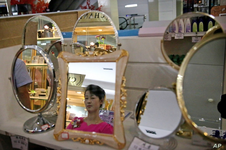 A staff member is reflected in a mirror for sale at the Potonggang department store in Pyongyang, North Korea, June 19, 2017.