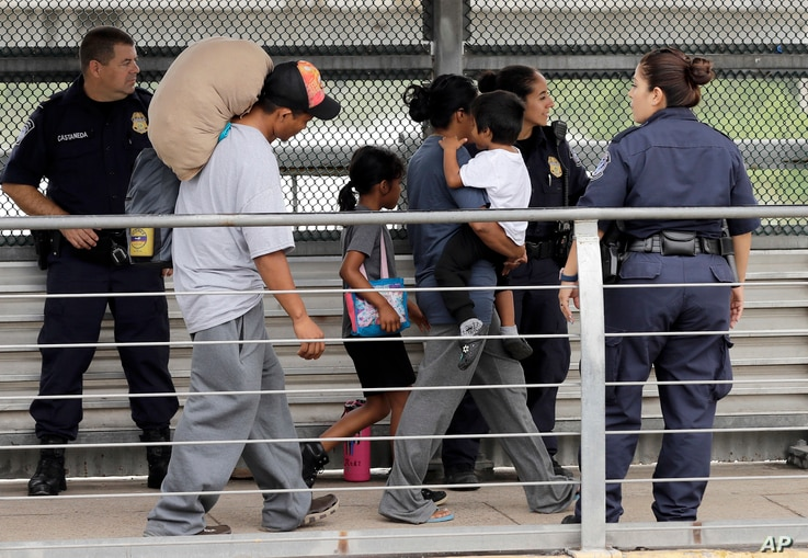 Ever Castillo, left, and his family, immigrants from Honduras, are escorted back across the border by U.S. Customs and Border Patrol agents, June 21, 2018, in Hildalgo, Texas. The parents were told they would be separated from their children and volu