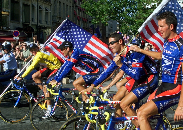 July 25, 1999: Lance Armstrong wins his first Tour de France, riding down the Champs Elysees with teammates in Paris.