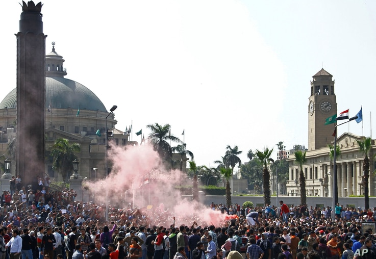 A cloud of red smoke from flares fills the air as supporters of ousted President Mohamed Morsi chant slogans during a demonstration outside Cairo University in Giza, March 26, 2014.