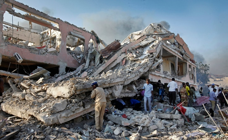 FILE - In this Oct 14, 2017, file photo, people gather to search for survivors by destroyed buildings at the scene of a blast in the capital Mogadishu, Somalia.