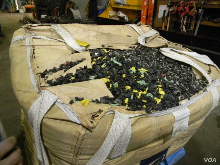 A load of shredded plastic gas tanks, removed from junkyard automobiles, awaits its turn with the plastic-eating monster. (VOA/D. Robison)