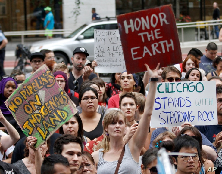 Protesters against the four-state Dakota Access pipeline hold signs during a rally in Chicago, Sept. 9, 2016.
