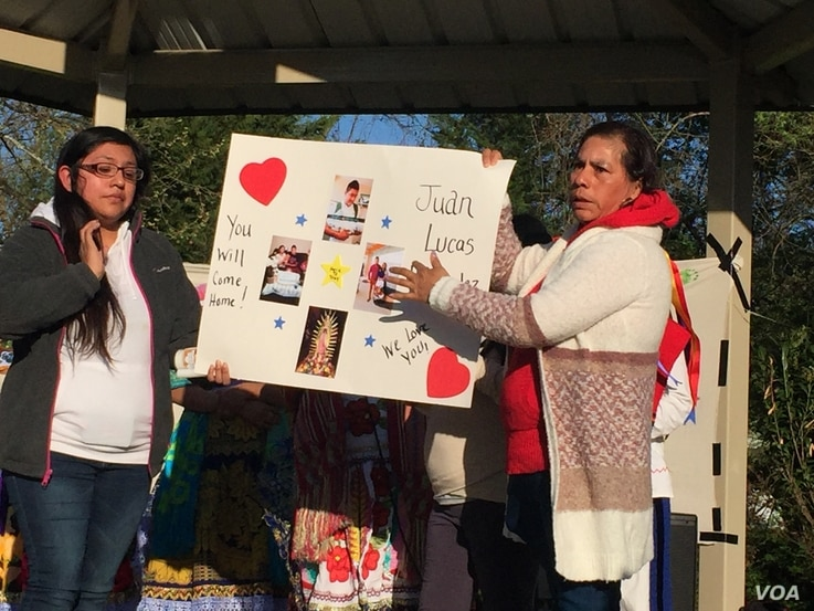 At a prayer vigil, family members hold up a poster calling for the return of one of the detained workers. (Photo: Marissa Melton / VOA)