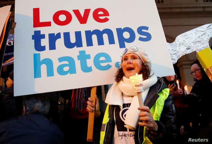 """A woman holds a sign and a candle as she takes part in the women's rights event """"Lights for Rights"""", a protest against the inauguration of Donald Trump as new U.S. president, in front of the Theatre Royal de la Monnaie in Brussels, Belgium, Jan. 20, ..."""
