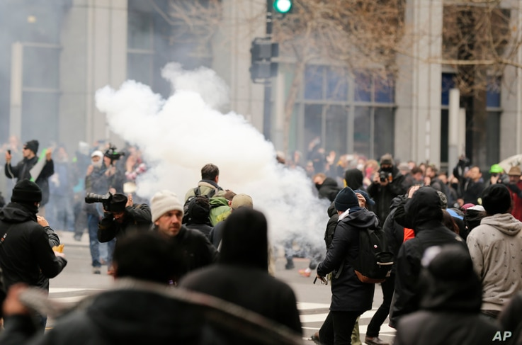 Police deploy smoke and pepper grenades during clashes with protesters in northwest Washington, on Inauguration Day, Jan. 20, 2017.