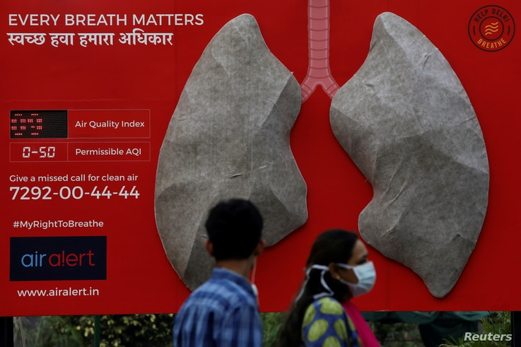 People pass by an installation of an artificial model of lungs to illustrate the effect of air pollution outside a hospital in New Delhi, India, Nov. 5, 2018.