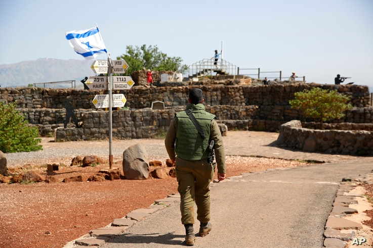 An Israeli soldier walks in an old military outpost, used for visitors to view the Israeli-controlled Golan Heights, near the border with Syria, May 10, 2018.