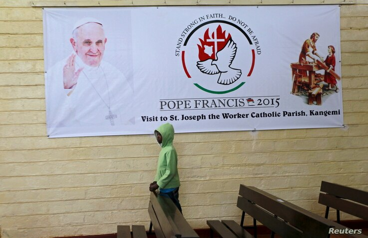 A boy is pictured below a banner of Pope Francis before a special mass at St. Joseph the Worker Catholic Parish where Pope Francis is expected to visit Kangemi, a slum that is home to 650,000 people in Kenya's capital Nairobi, Nov. 22, 2015.