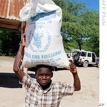 A Haitian child carries a bag of food during a WFP food distribution in Balan, a suburb of Ganthier, 12 Nov 2009