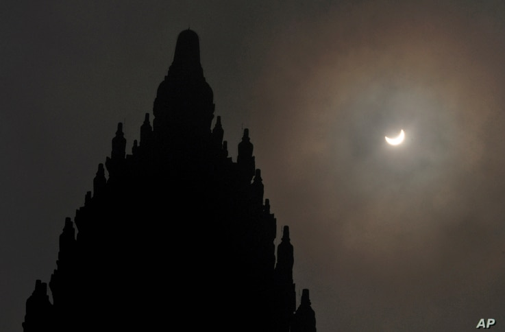 A partial solar eclipse is seen behind the 9th century Prambanan Temple in Yogyakarta, Indonesia, Wednesday, March 9, 2016.