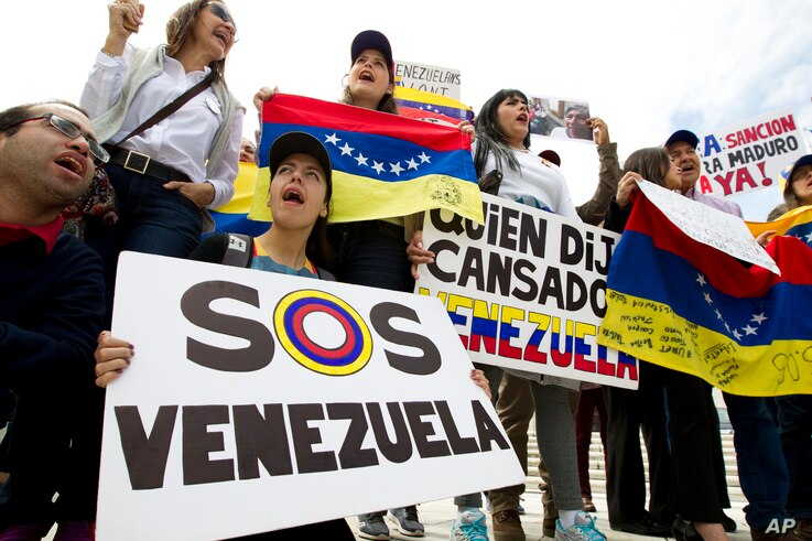 FILE - Demonstrators who are against the Venezuelan government chant outside of the Organization of American States (OAS) during the special meeting of the Permanent Council, in Washington.