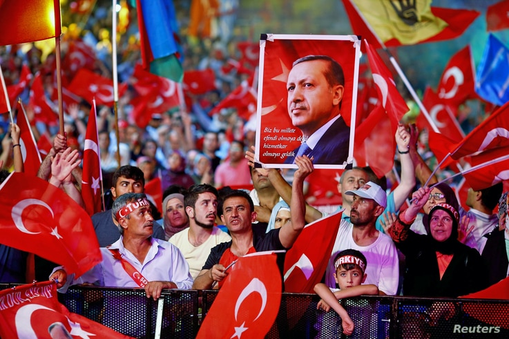 Supporters of Turkish President Recep Tayyip Erdogan wave national flags as they listen to him through a giant screen in Istanbul's Taksim Square, Turkey, Aug. 10, 2016.