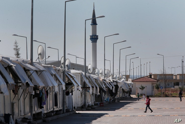 Refugees walk at the Oncupinar refugee camp for Syrian refugees next to the border crossing with Syria, near the town of Kilis in southeastern Turkey, Thursday, March 17, 2016.