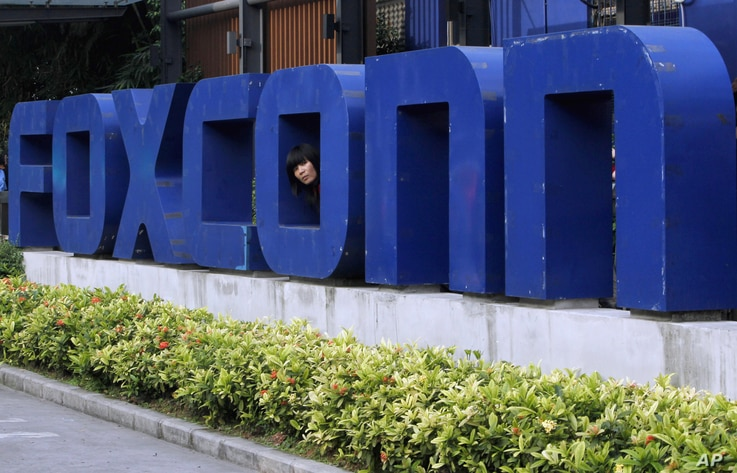 FILE - A worker looks out through the logo at the entrance of the Foxconn complex in the southern Chinese city of Shenzhen, May 27, 2010.