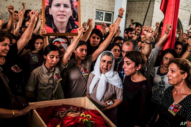 Mourners chant slogans as they gather around the body of Gulay Ozarlan, a DHKP-C militant, who was killed during a major police sweep that was launched against the outlawed group as well as suspected members of the outlawed Kurdish rebel group, and a...