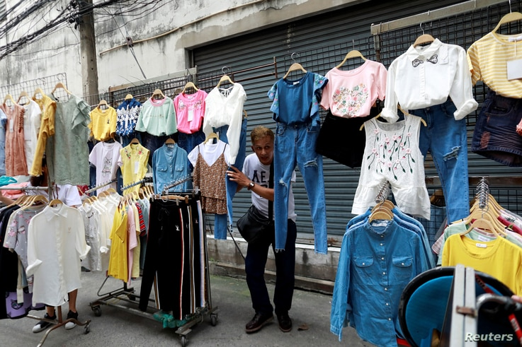 A street vendor holds his clothes when police take action on a street in Bangkok, Thailand,  Sept. 12, 2018.