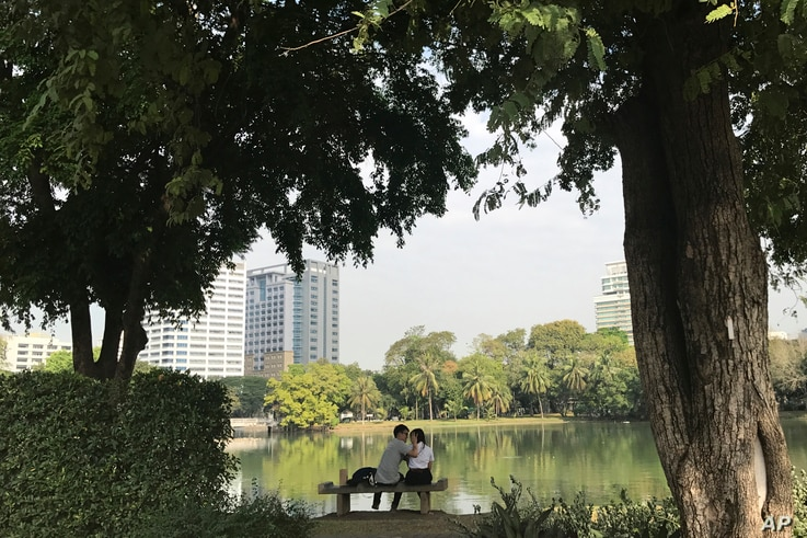 In this Feb. 2, 2017, photo, a couple sit on a bench in front of a lake in Lumpini Park in Bangkok, Thailand.