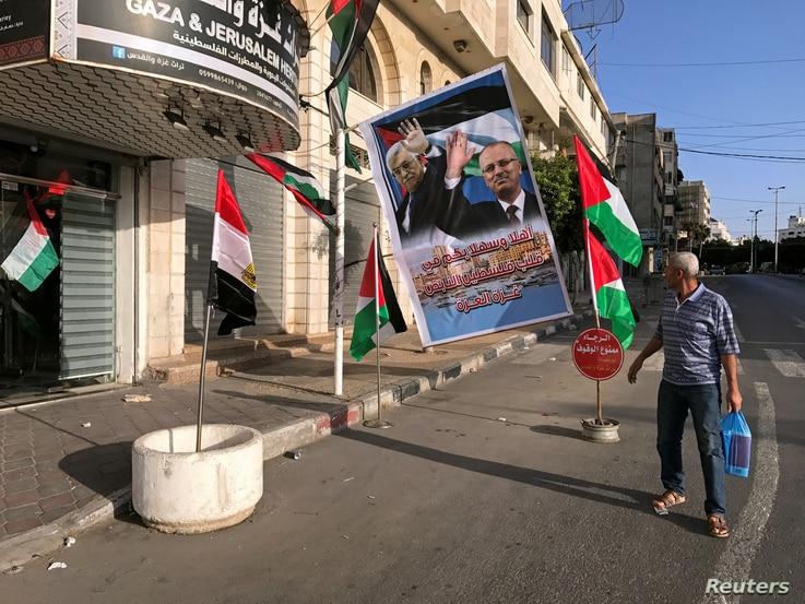 A man looks at a poster depicting Palestinian President Mahmoud Abbas and Prime Minister Rami Hamdallah in Gaza City, Oct. 1, 2017.