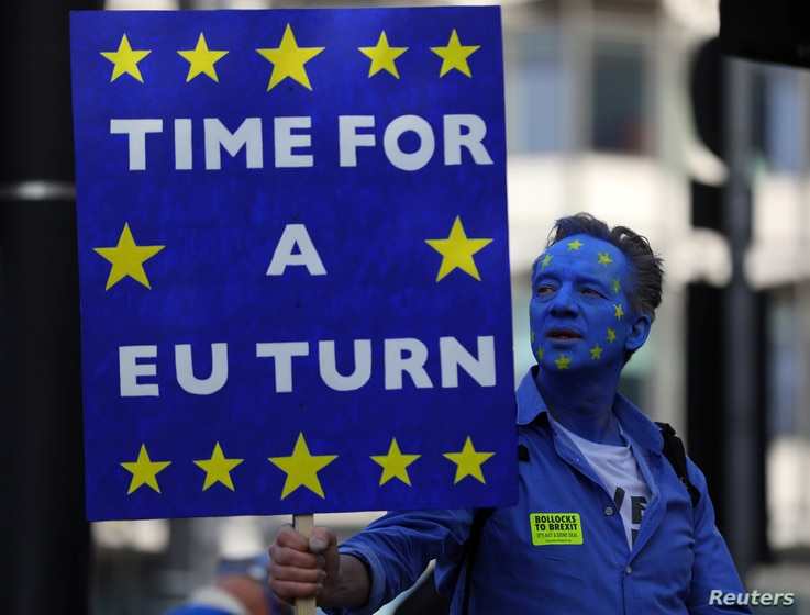 A protester holds a banner before an anti-Brexit demonstration, in central London, Britain, Oct. 20, 2018.
