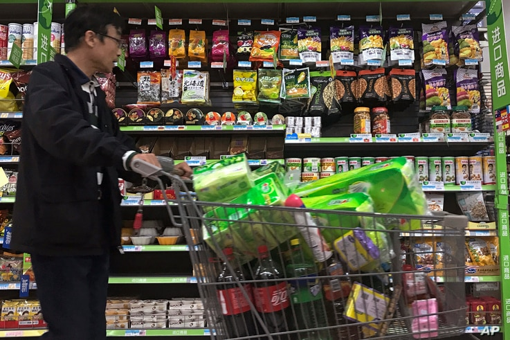 A man pushes a shopping cart past a display of nuts imported from the United States and other countries at a supermarket in Beijing, April 2, 2018. China raised import duties on a $3 billion list of U.S. pork, fruit and other products Monday in an es