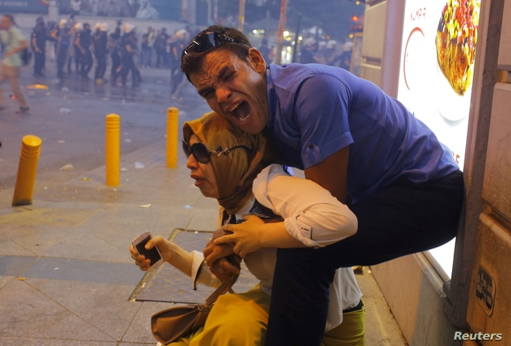 A couple, affected by tear gas used by riot police to disperse demonstrators, reacts in central Istanbul, Turkey, July 20, 2015.