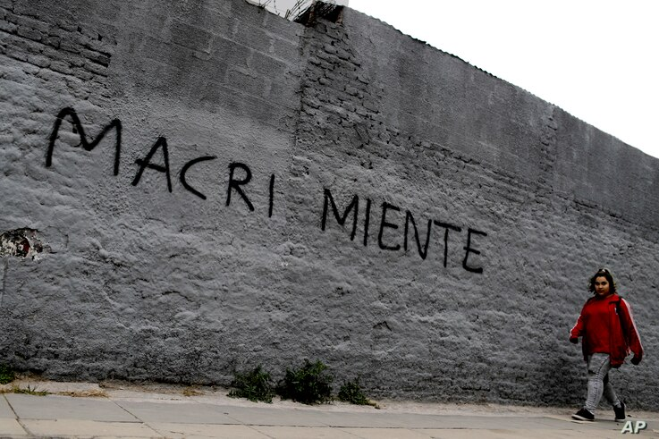 "A woman walks past a wall spray-painted with a message that reads in Spanish ""Macri lies"" in reference to the country's president, Mauricio Marci, in Buenos Aires, Argentina, Aug. 30, 2018. Argentina's Central Bank on Thursday increased its benchma..."