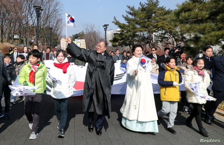 South Korean President Moon Jae-in and his wife Kim Jung-Sook march with participants during a ceremony celebrating the 99th anniversary of the March First Independence Movement against Japanese colonial rule in Seoul, South Korea, March 1, 2018.