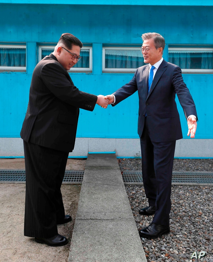 North Korean leader Kim Jong Un, left, shakes hands with South Korean President Moon Jae-in over the military demarcation line at the border village of Panmunjom in Demilitarized Zone, April 27, 2018.