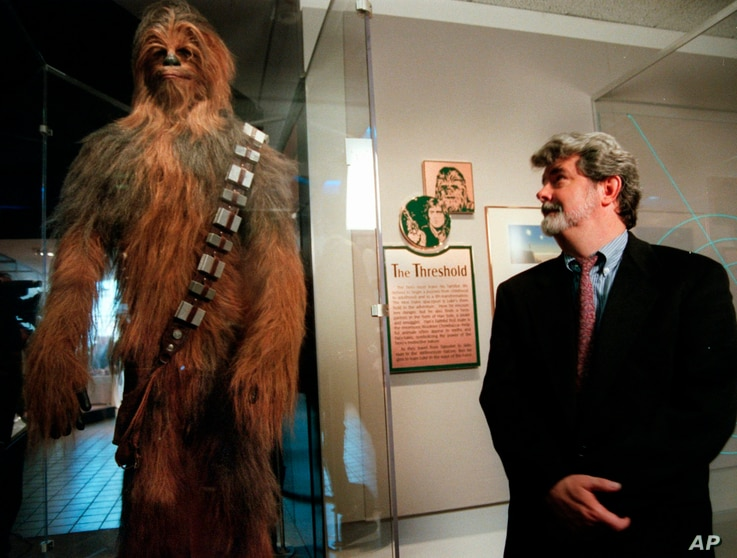 """FILE - In this Oct. 29, 1997 file photo, filmmaker George Lucas looks over a Chewbacca costume at the """"Star Wars"""" exhibit at the Smithsonian Institution's Air and Space Museum in Washington."""