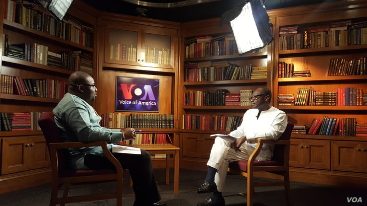 Ghana's finance minister, Ken Ofori-Atta, at right, speaks with VOA's Peter Clottey.