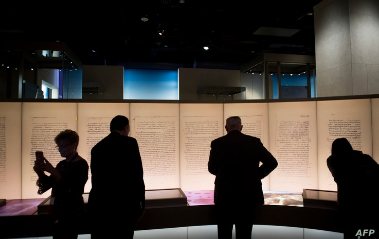 FILE - Visitors look at an exhibit about the Dead Sea Scrolls during a media preview of the Museum of the Bible in Washington, D.C., Nov. 14, 2017. The museum announced on Oct. 22, 2018, that five artifacts it had said were fragments of the ancient m...