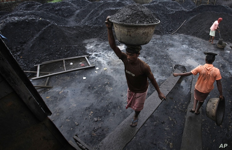 Workers load coal onto a truck at a coal depot in Gauhati, India, August 22, 2012.