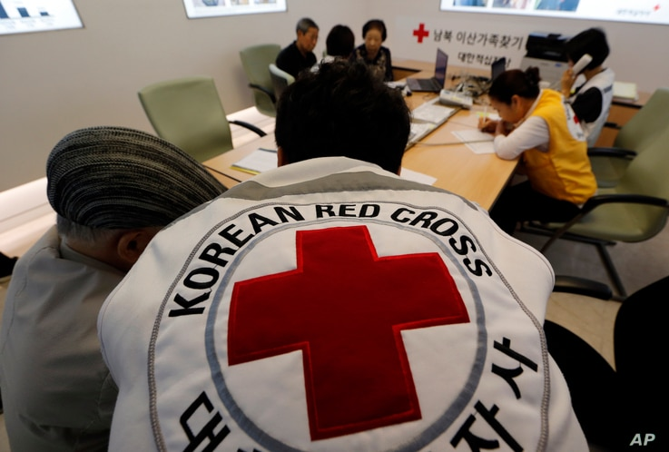 South Koreans who were separated from their families during the Korean War, talk with Red Cross members as they check application forms to reunite with their family members living in North Korea, at the Korea Red Cross headquarters in Seoul, South Ko...