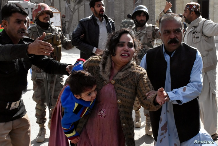 A policeman guides a family away from the Bethel Memorial Methodist Church in Quetta, Pakistan, after gunmen attacked, Dec. 17, 2017.
