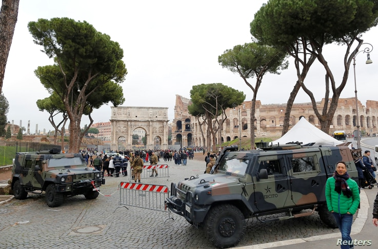 Armed Italian soldiers patrol a busy public area around the Colosseum ahead of New Year's Eve celebrations in Rome,  Dec. 30, 2017.
