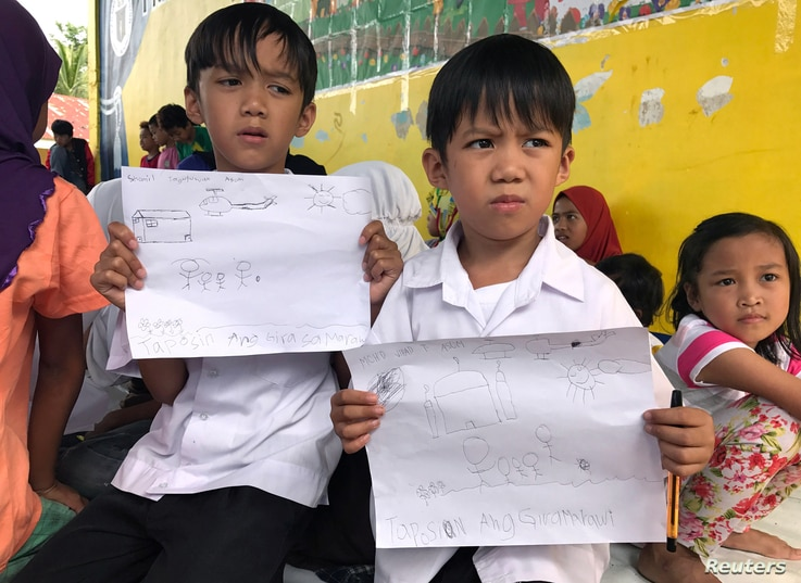 Evacuated students show their drawings about what they and other Marawi residents experienced before fleeing the city still under siege during a school day at Pantar elementary school in Lanao Del Norte, Philippines, June 6, 2017.