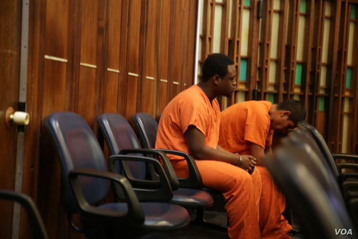 Defendants in orange prison jumpsuits and handcuffs wait for Judge Jeri Cohen's determination of whether they should go back to jail or be placed in a treatment program. The defendants were arrested in Miami, Fla., on charges of using and possessin...