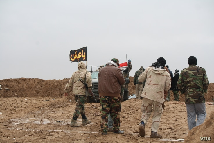 As the weather turns cold, and deserts turn into mud fields, predominantly Shia militias known locally as Hashd Shaabi, or Popular Mobilization forces, man berms against continued Islamic State attacks in Nineveh province, Iraq, Dec. 15, 2016. (H. Mu...