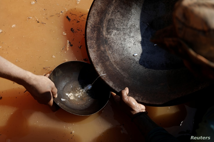 Miners rub mercury that has coagulated into tiny particles of gold in a basin at a mine near Crepurizao, Brazil, Aug. 5, 2017.