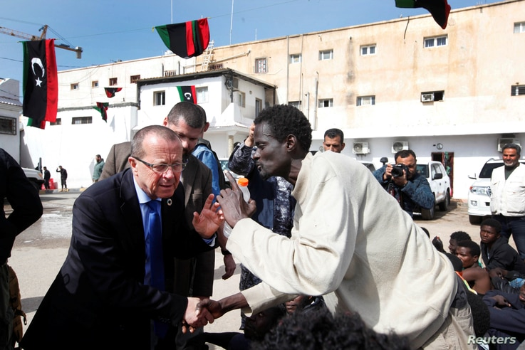 U.N. Special Representative and Head of the United Nations Support Mission in Libya, Martin Kobler listens to an African migrant during a visit to a detention camp in Tripoli, Libya, Feb. 21, 2017.