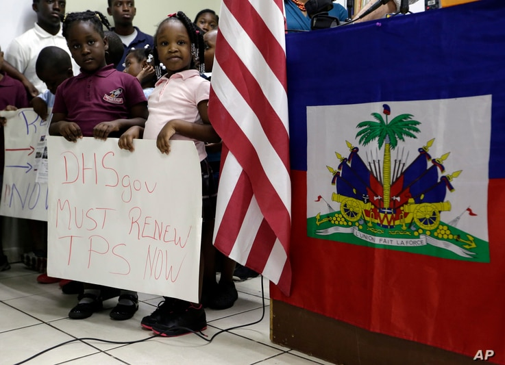 Children stand next to United States and Haitian flags as they hold signs in support of renewing Temporary Protected Status (TPS) for immigrants from Central America and Haiti now living in the United States, during a news conference, Nov. 6, 2017, i...