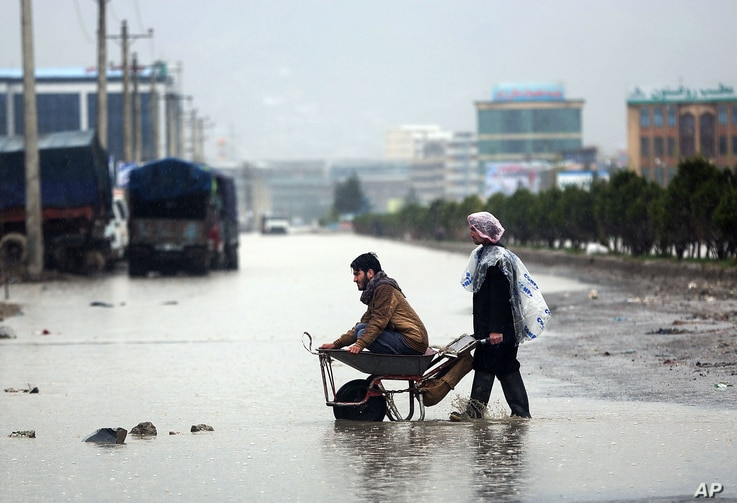 Afghans make their way in flooded water from heavy rain  in Kabul, Afghanistan, April 2, 2016.